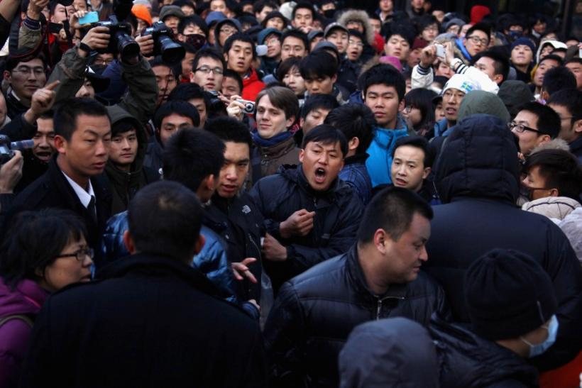 A man yells at a security guard after the guard tried to remove a member of the crowd at the Apple store in the Beijing district of Sanlitun