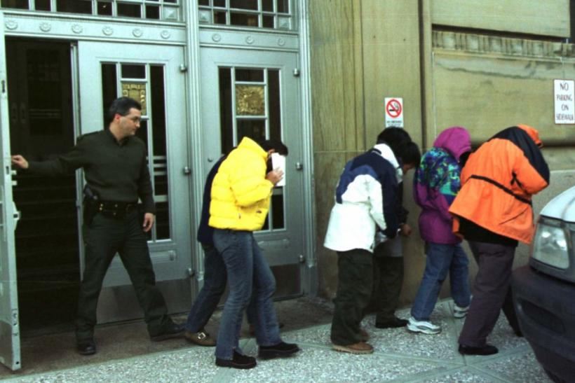 U.S. Immigration officers escort six Chinese citizens from Federal Court in Buffalo as they were ordered returned to Canada where they will await asylum.