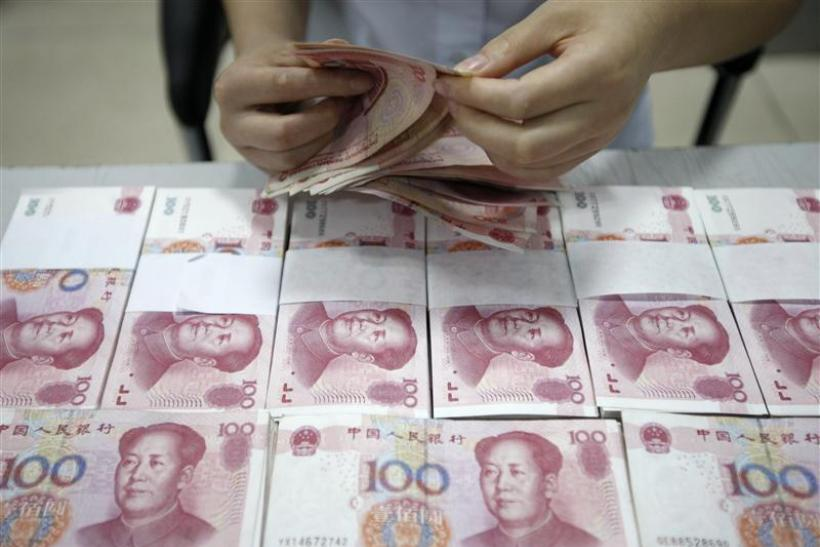 An employee counts yuan banknotes at a bank in Huaibei