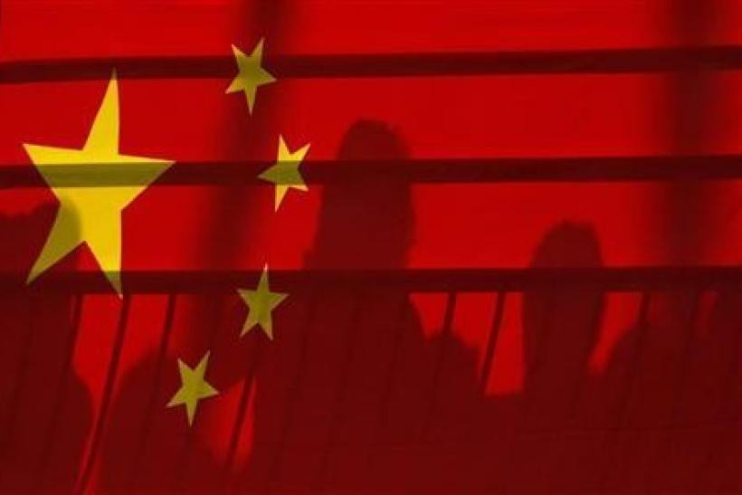 The shadows of spectators are seen through a Chinese national flag during the men's kayak (K1) semifinal at the Beijing 2008 Olympic Games August 12, 2008.