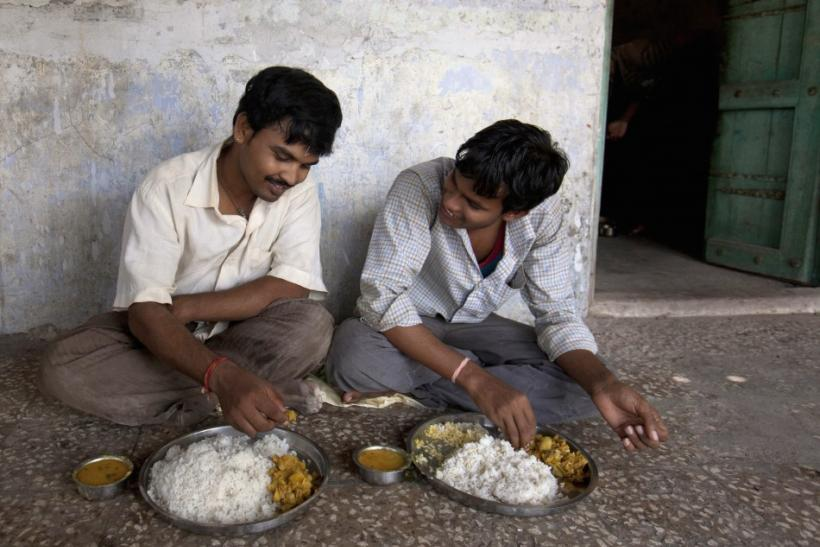 Unmarried men eat lunch together in the remote village of Siyani, India