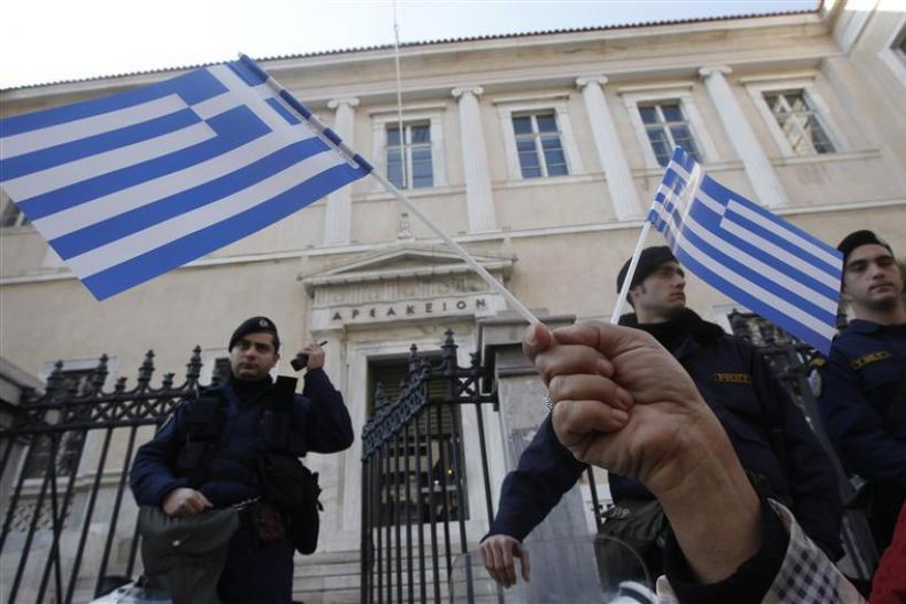 A protester holds Greek flags during a demonstration against a new property tax which has been included to the Greece's PPC bill to consumers in Athens.