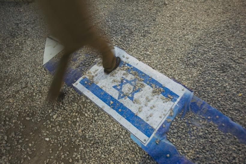 EDITORS' NOTE: Reuters and other foreign media are subject to Iranian restrictions on leaving the office to report, film or take pictures in Tehran. An Iranian man walks on an Israeli flag while visiting a war exhibition held by Iran's revolutio