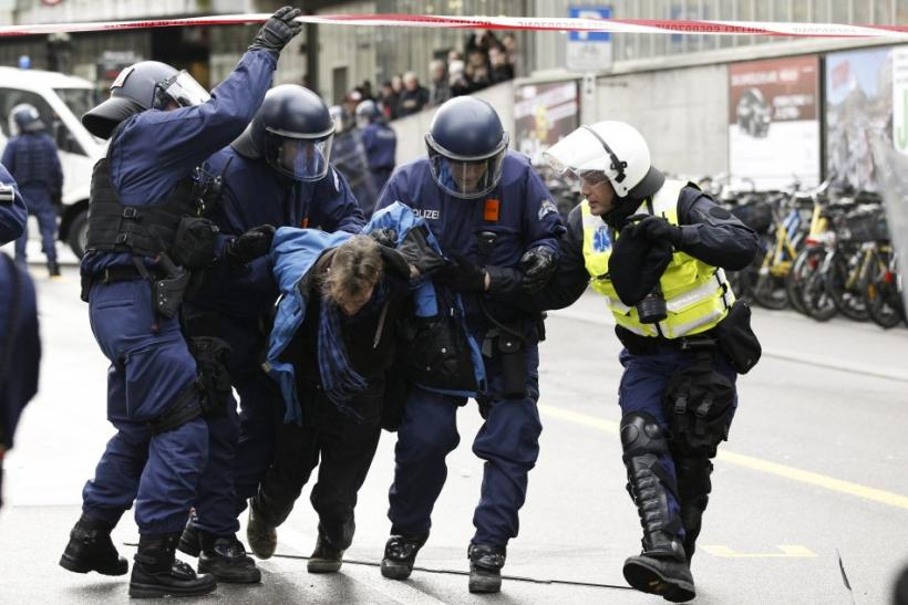 Swiss riot police remove an anti World Economic forum ( WEF) protestor during a demonstration in Bern January 21, 2012. The WEF will take place in Davos January 25 - 29.