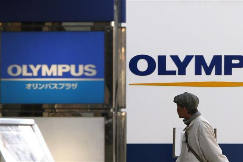 A man walks past signboards of Olympus Corp outside its showroom in Tokyo