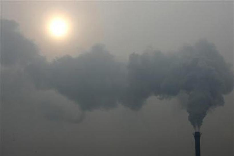 A chimney billows smoke as the sun shines through haze on a cold winter's day in Beijing December 24, 2009.