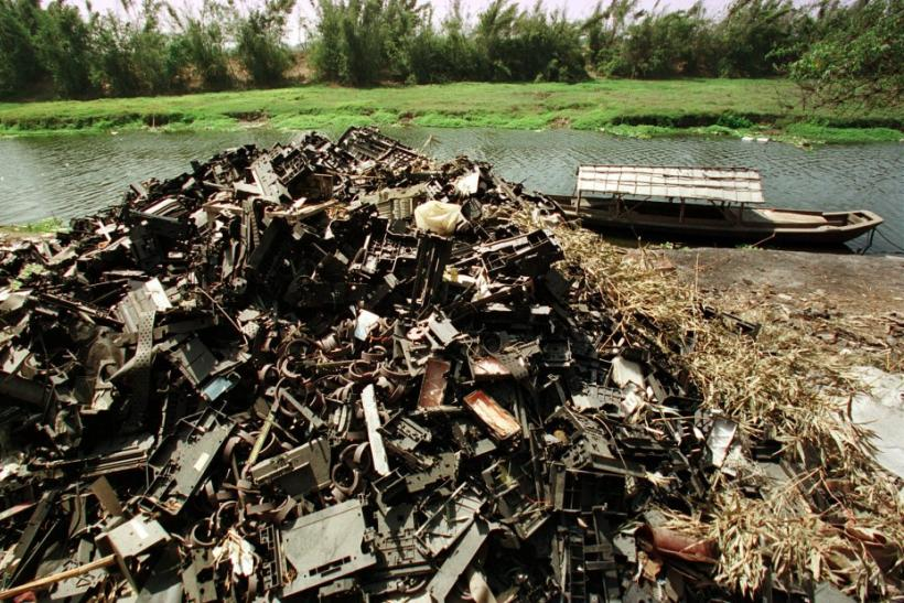 Computer waste is left along a river bank at Yaocuowei village near Guiyu in China. This image is taken from 2002.