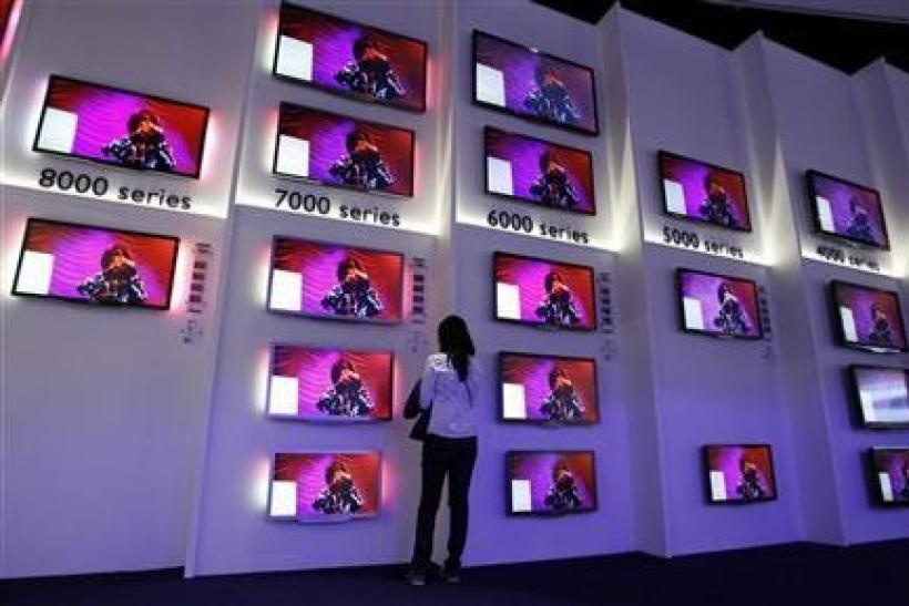 A woman looks at flat screen TV sets in the Philips pavilion before the opening of the IFA consumer electronics fair in Berlin, August 31, 2011.