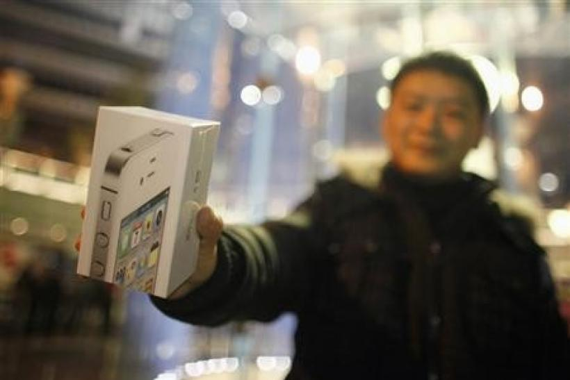 A customer show his new iPhone 4S after making the purchase at Apple's retail store in downtown Shanghai January 13, 2012.