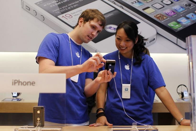 Apple employees look over the new iPhone 4S at Apple's flagship retail store in San Francisco