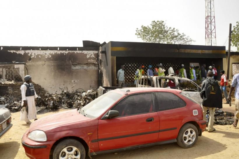 People stand in front of a police headquarters after a bomb attack in Nigeria's northern city of Kano January 21, 2012.