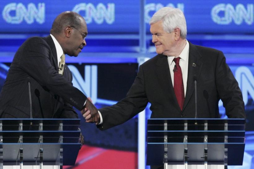 U.S. Republican presidential candidates businessman Herman Cain and former U.S. House Speaker Newt Gingrich (R) shake hands at the end of the CNN GOP National Security debate in Washington, November 22, 2011.