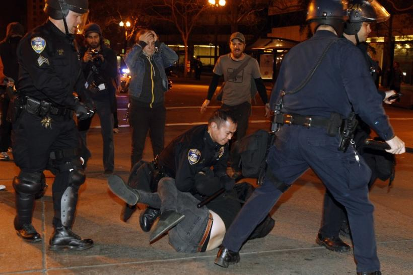 A group of police officers from various law enforcement agencies arrest an Occupy Oakland demonstrator near Frank H. Ogawa Plaza during a day-long protest in Oakland, California January 28, 2012.
