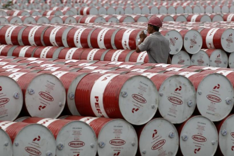 A worker walks in between oil barrels at Pertamina's storage depot in Jakarta, Indonesia, on Jan. 26, 2011.
