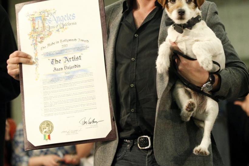 "French actor Jean Dujardin and the dog Uggie pose at a ceremony where the cast and crew of the film ""The Artist"" received the inaugural ""Made in Hollywood"" commendation at Red Studios in Los Angeles"
