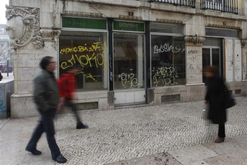 People walk near a closed down shop in downtown Lisbon
