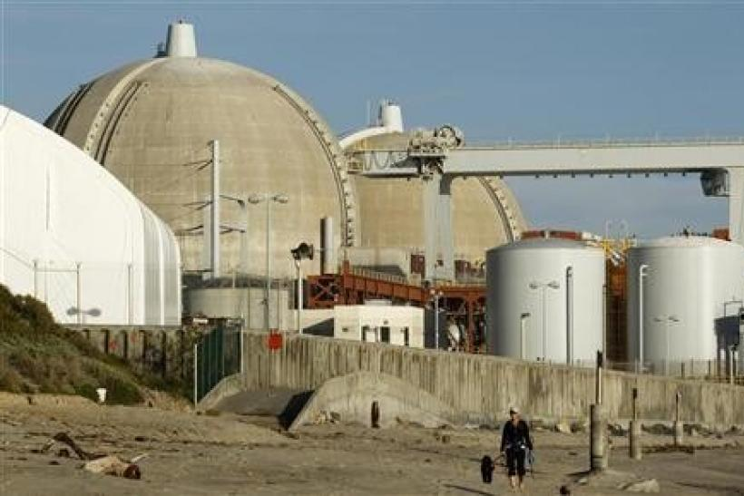 A woman and her dogs walk past the San Onofre Nuclear Generating Station that sits on the shore of the Pacific Ocean in North San Diego County, California