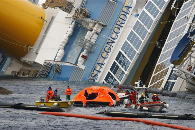 Firefighters tow an abandoned life raft from the capsized cruise liner Costa Concordia off the west coast of Italy at Giglio island