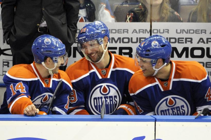 Sam Gagner (C) talks with linemates Jordan Eberle (L) and Taylor Hall on the bench after scoring his fourth goal against the Chicago Blackhawks.