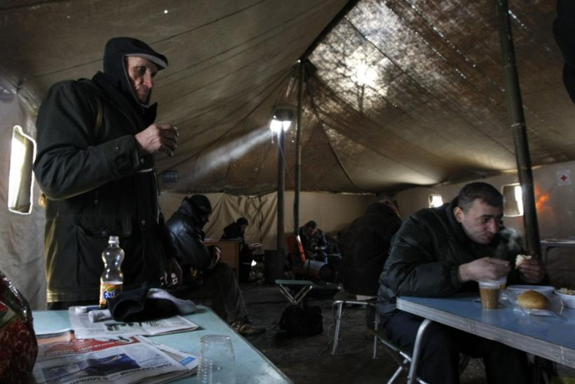 Homeless people have a hot meal provided by local authorities as they warm up at a tent camp set up to provide shelter against cold weather in Kiev