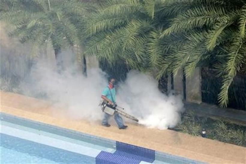 A worker 'fogs' in the public area of a private condominium in Singapore, May 24, 2006.