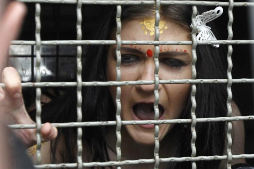 A detained activist from women's rights group Femen shouts from a police van during a protest in front of the residence of the Indian ambassador in Kiev