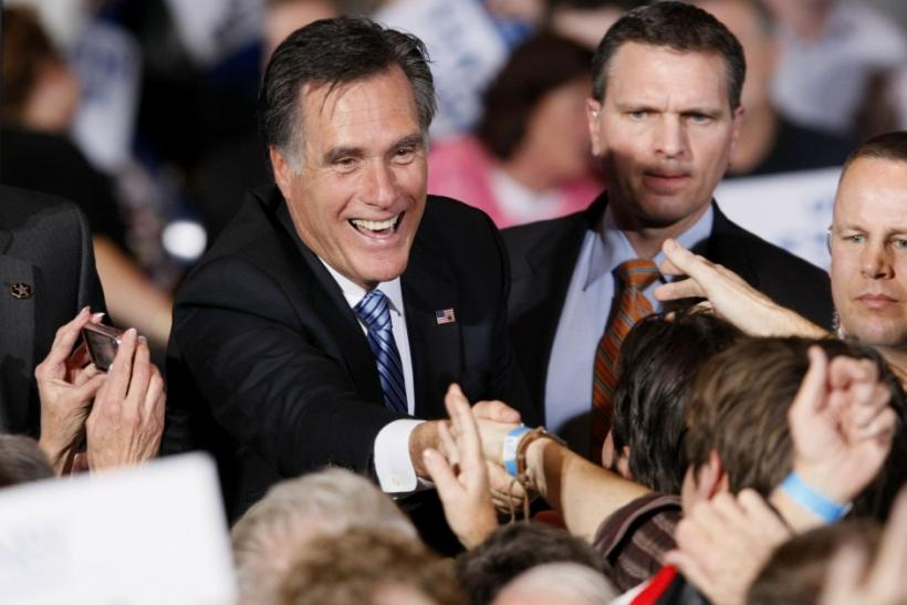U.S. Republican presidential candidate and former Massachusetts Governor Mitt Romney shakes hands with supporters while giving a speech at his Nevada caucus night rally in Las Vegas, Nevada, Feb. 4, 2012.
