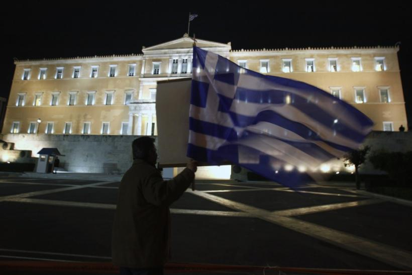 An anti-government protester holds a Greek flag as he shouts slogans against Greek Premier George Papandreou and his lawmakers in front of the parliament during a debate prior to a vote of confidence in Athens November 3, 2011.