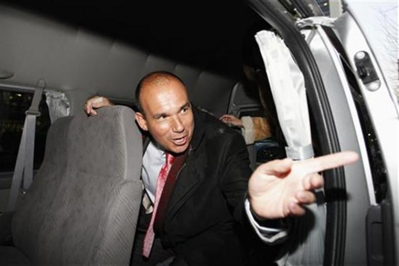Former Olympus CEO Michael Woodford speaks to a reporter from inside a van as he leaves a news conference in Tokyo