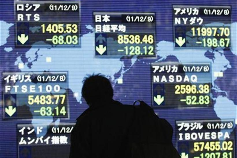A man looks at an electronic board displaying a fall in major market indices around the world outside a brokerage in Tokyo