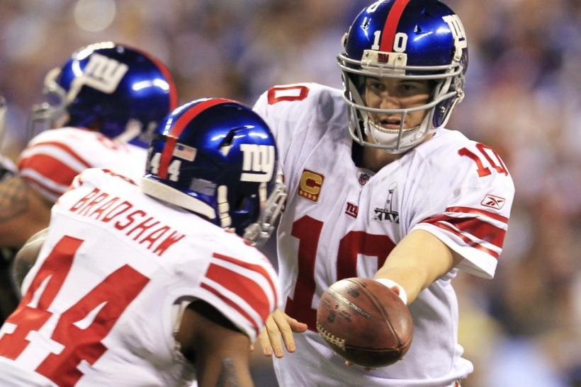 New York Giants quarterback Eli Manning (R) hands off to running back Ahmad Bradshaw during first quarter play against the New England Patriots in the NFL Super Bowl XLVI football game in Indianapolis, Indiana