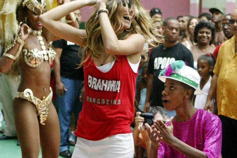 Brazilian super model Gisele Bundchen (far R) dances with carnival queens and revelers at the Mangueria samba school square in Rio de Janeiro, February 20, 2004.