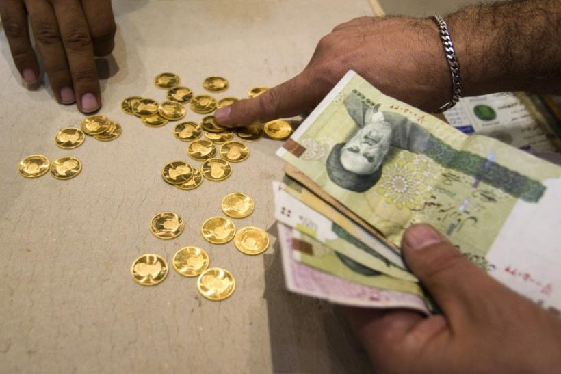 A customer buys Iranian gold coins at a currency exchange office in Tehran