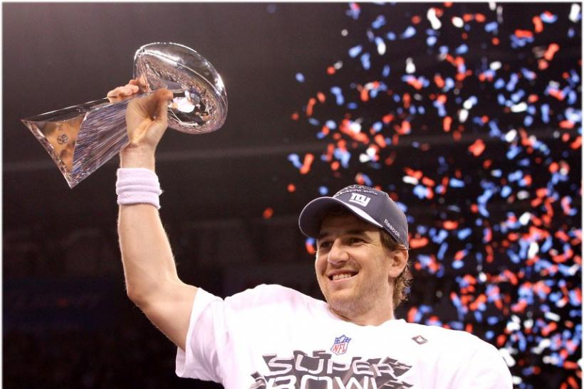 New York Giants quarterback Eli Manning holds up the Vince Lombardi Trophy after defeating the New England Patriots in the NFL Super Bowl XLVI football game in Indianapolis