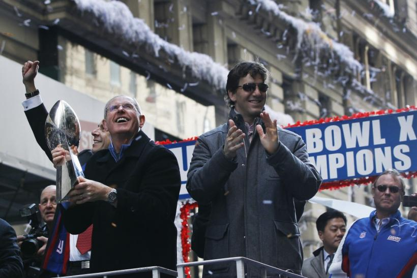 New York Giants head coach Tom Coughlin (L) holds the Super Bowl Trophy as quarterback Eli Manning smiles during the team's ticker tape Super Bowl victory parade through the Canyon of Heroes along Broadway in New York