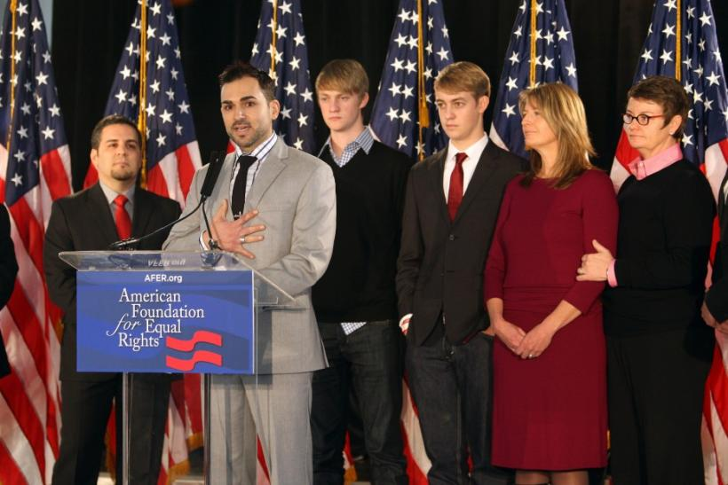 Paul Katami addresses a news conference as his partner Jeff Zarillo (L), and Kris Perry and her partner Sandy Stier (R) look on with their sons Elliot Perry and Spencer Perry (center R) after the United States Court of Appeals for the Ninth Circuit declar