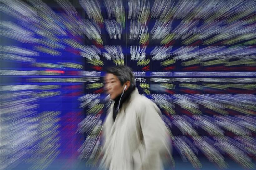 A man walks past a stock quotation board showing Japanese companies' stock prices outside a brokerage in Tokyo