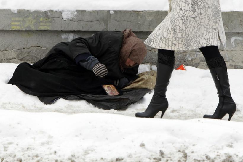 Woman begs for money as people pass by, with the air temperature at about minus 13 degrees Celsius, in Kiev