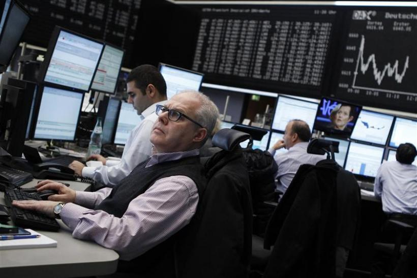 Traders work at their desks at the Frankfurt stock exchange