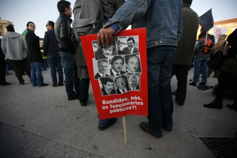 A demonstrator holds a banner depicting Portugese politicians and German Chancellor Angela Merkel as Adolf Hitler during a protest in Lisbon February 11, 2012.