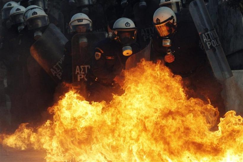 A petrol bomb explodes near riot police during an anti-austerity demonstration in Athens