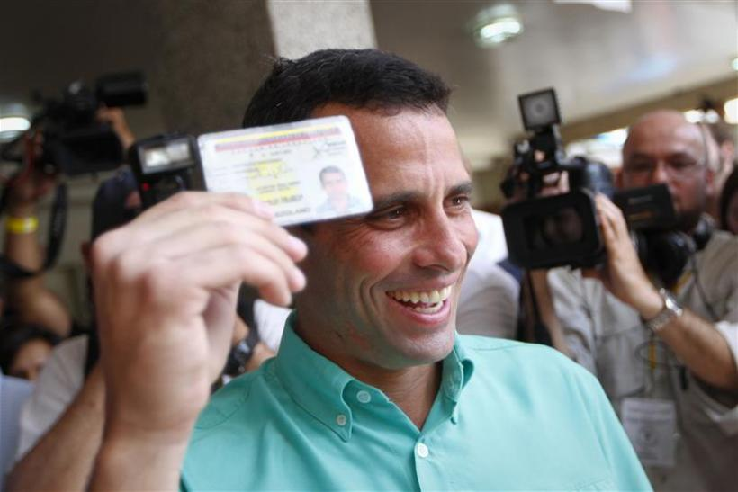 Opposition presidential candidate and Miranda state Governor Henrique Capriles smiles as he arrives to cast his vote at a polling station in Caracas