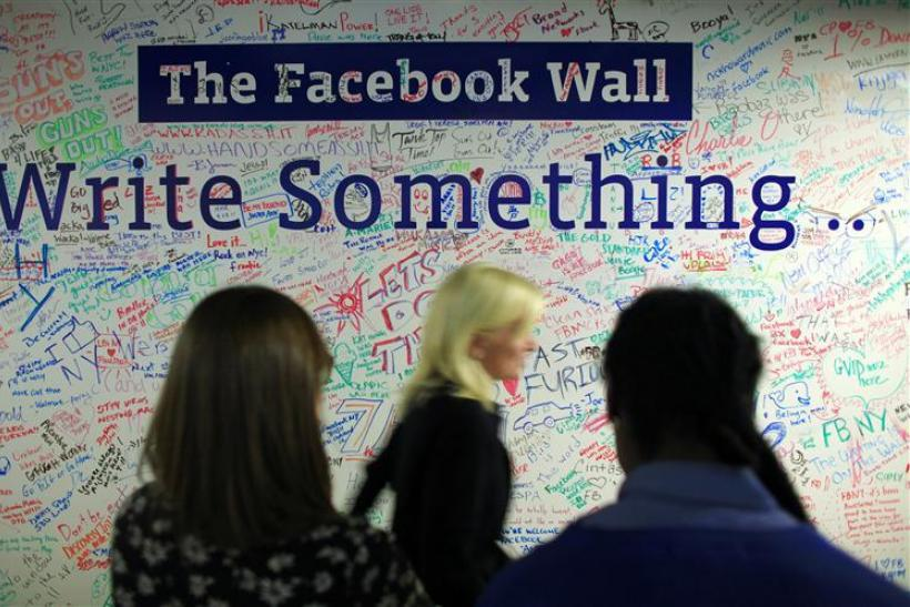 People walk past the Facebook wall inside their office in New York