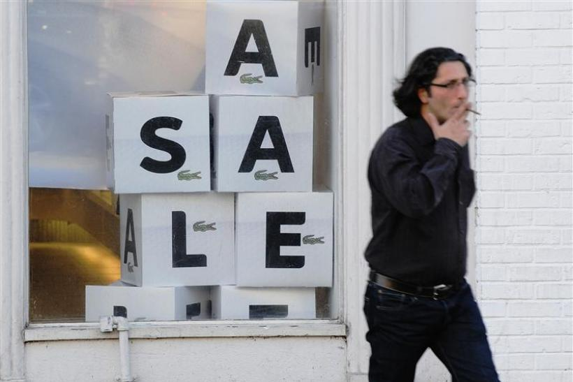 "A man walks past a ""sale"" sign in the Georgetown shopping district in Washington"