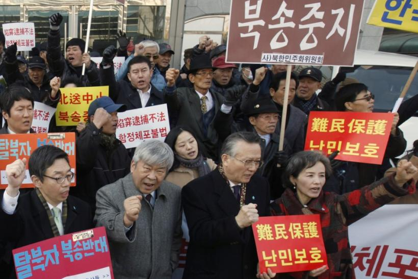 Protesters attend rally held by former North Korean defectors and anti-North Korean activists near the Chinese Embassy in Seoul