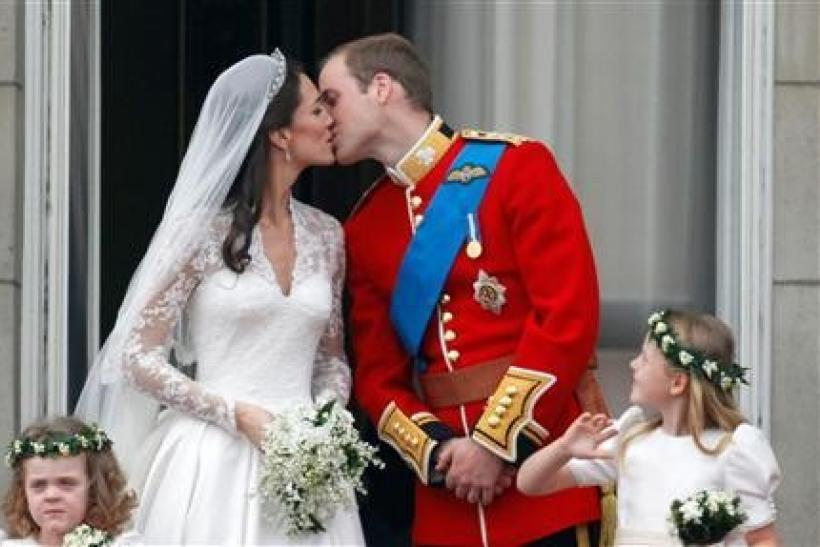 Britain's Prince William and his wife Catherine, Duchess of Cambridge, kiss as they stand on the balcony at Buckingham Palace with other members of the Royal Family, after their wedding in Westminster Abbey, in central London