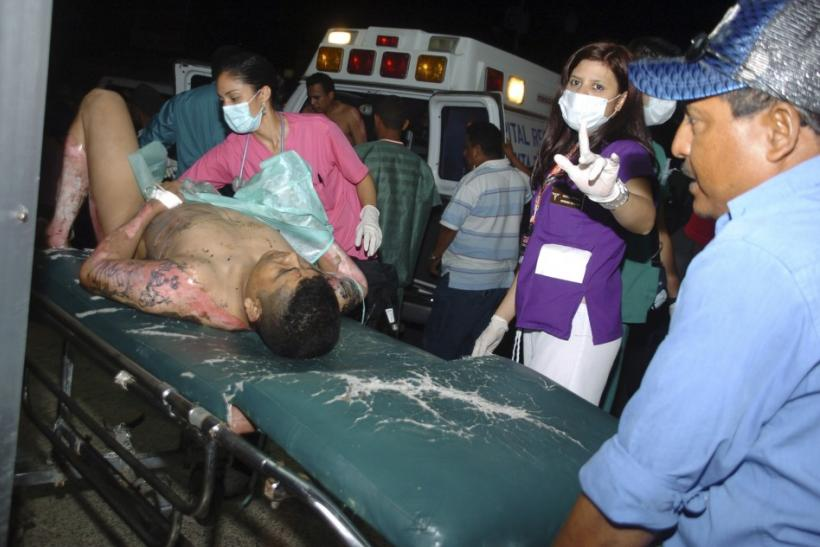 An injured man is wheeled into Escuela hospital in Tegucigalpa, after a blaze that began late on Tuesday night in Comayagua