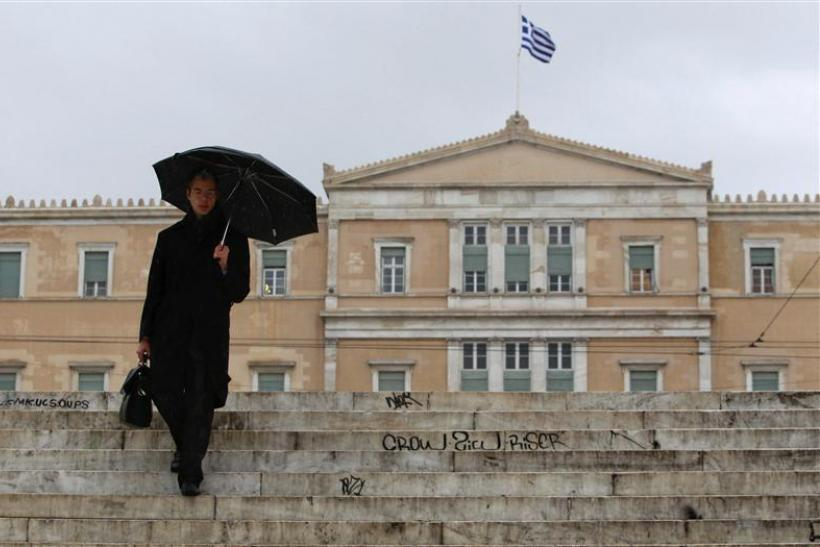 A man makes his way during a rainy day in front of the parliament in Athens
