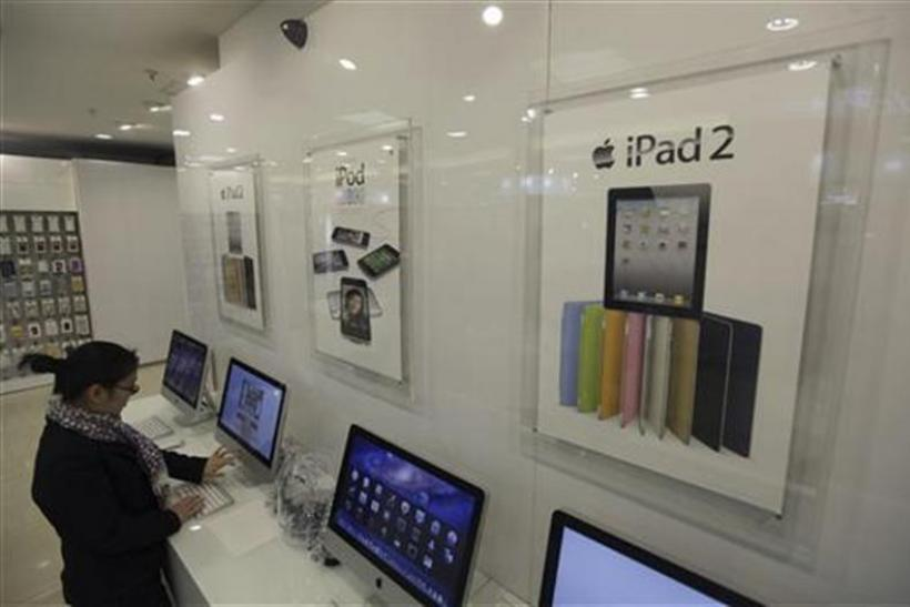 Apple iPad posters are seen at a dealership as a customer tries out an Apple Mac in Wuhan