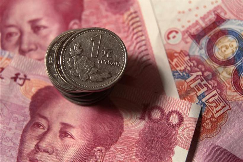 Chinese one yuan coins are placed on 100 yuan banknotes in this illustrative photograph taken in Beijing